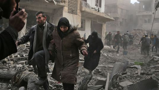 A member of the Syrian civil defence speaks on a wireless transmitter as other civilians flee