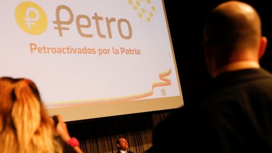 The new Venezuelan cryptocurrency the Petro logo is seen as Minister for University Education, Science and Technology Hugbel Roa talks to the media during a news conference in Caracas, Venezuela, January 31, 2018.