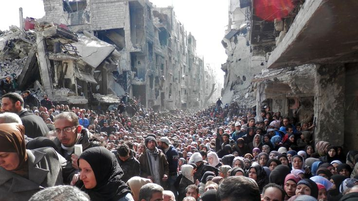 A now iconic image showed crowds of people queuing for food aid at Yamouk camp