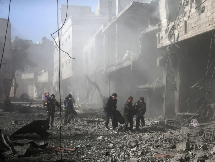 Syrian men carry an injured victim amid the rubble of buildings following government bombing in the rebel-held town of Hamouria