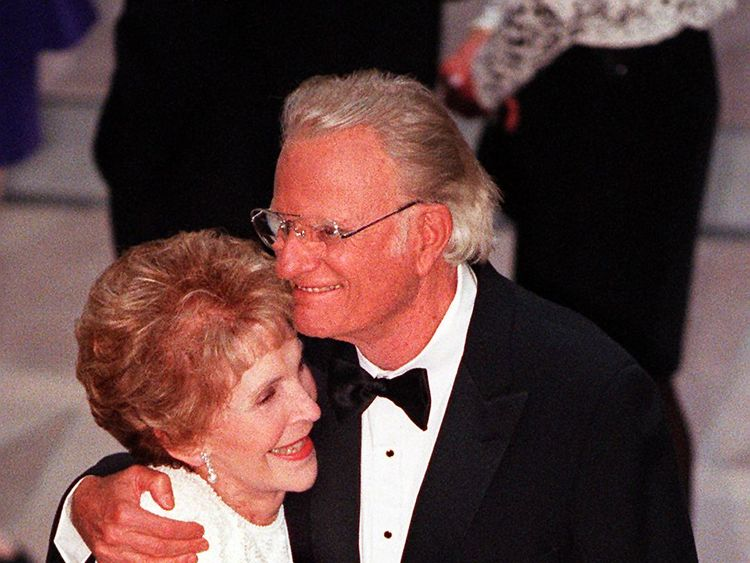 Former US First Lady Nancy Reagan (L) and Reverend Billy Graham embrace during the gala dedication of the Ronald Reagan Building