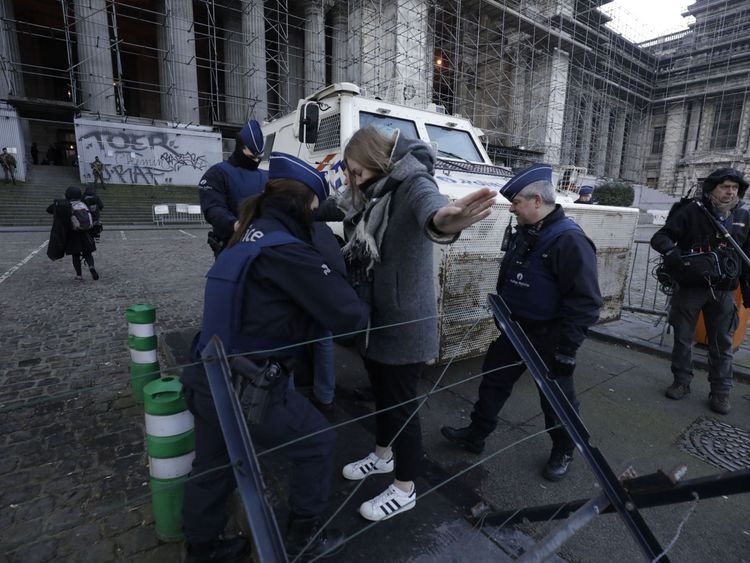 Police officers check people as they pass a security control check at the Brussels court