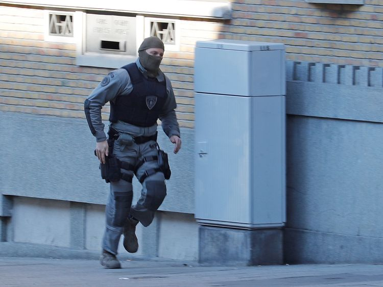 A Belgian police special forces member runs in the Forest commune after it was closed by Belgian police and special forces in Brussels