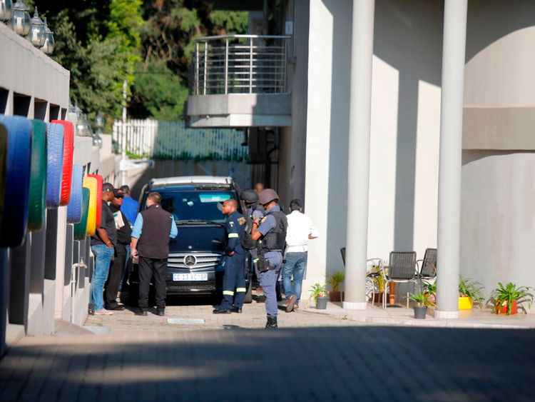 A police van and uniformed and plainclothes police officers inside the compound of the controversial business family Gupta