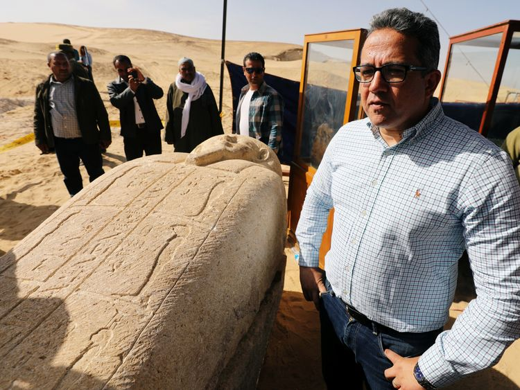 Minister of Antiquities Khaled El-Enany stands near a stone sarcophagi