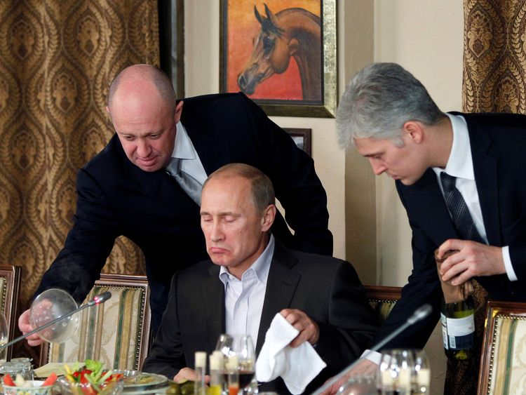 Evgeny Prigozhin (L) assists Vladimir Putin during a dinner in 2011