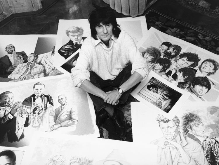 Guitarist Ronnie Wood of the Rolling Stones with some of his drawings of fellow musicians, 1987. (Photo by Daily Express//Hulton Archive/Getty Images)