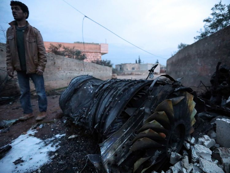 A Syrian man stands beside the engine of a shot-down Russian plane