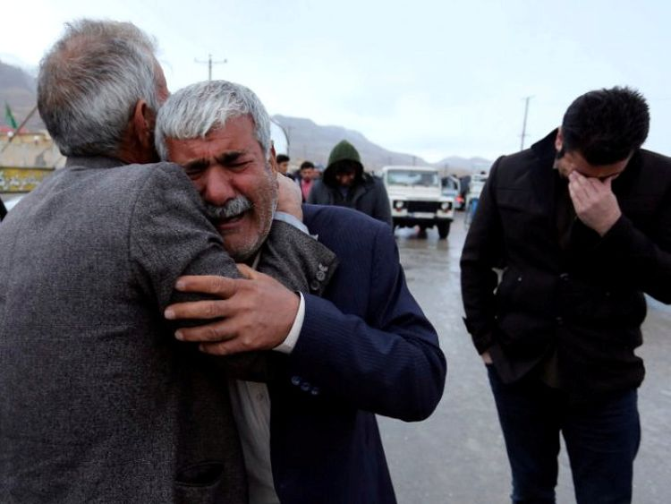 Relatives of passengers who were believed to have been killed in a plane crash react near the town of Semirom, Iran, February 18, 2018