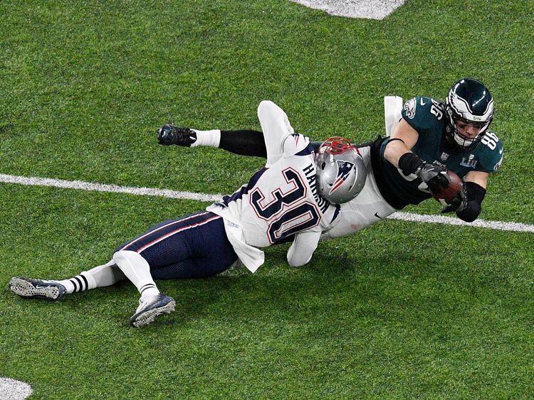 Zach Ertz of the Philadelphia Eagles makes a catch as he is tackled by Duron Harmon of the New England Patriots