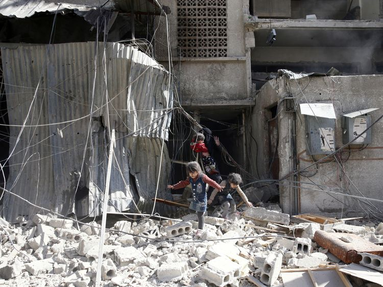 Children play in the rubble after the strikes