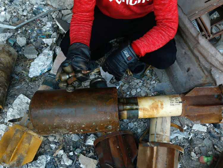 A Syrian man shows remnants of rockets reportedly fired by regime forces on the rebel-held besieged town of Douma