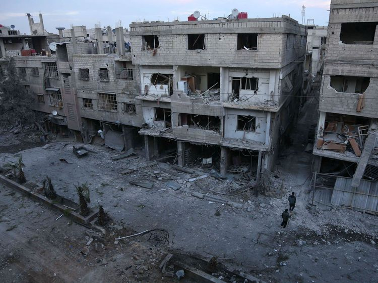 Syrian civilians look at the rubble following government bombing on the outskirts of the capital Damascus