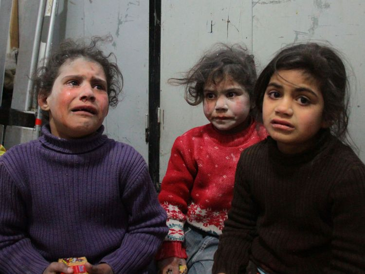 Syrian children cry at a make-shift hospital in Douma following air strikes on the Syrian village of Mesraba in the besieged Eastern Ghouta region