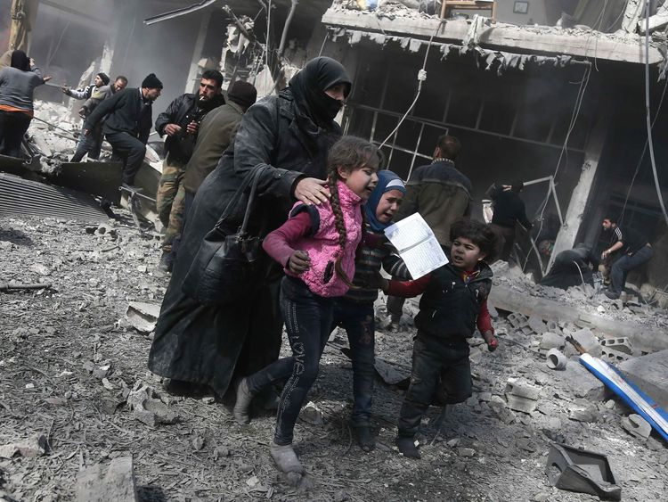 A Syrian woman and children run for cover after the air strikes