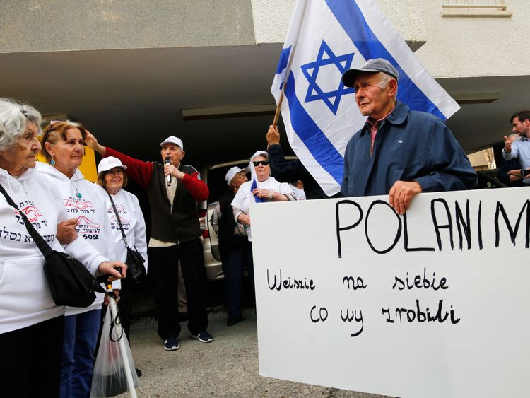 Holocaust survivors hold banners and wave an Israeli flag during a protest in front of Polish embassy in Tel Aviv on February 8, 2018, against a controversial bill passed by the eastern European country's senate. The legislation sets fines or a maximum three-year jail term for anyone describing Nazi German death camps in Poland, like Auschwitz-Birkenau, as Polish. / AFP PHOTO / GIL COHEN-MAGEN (Photo credit should read GIL COHEN-MAGEN/AFP/Getty Images)