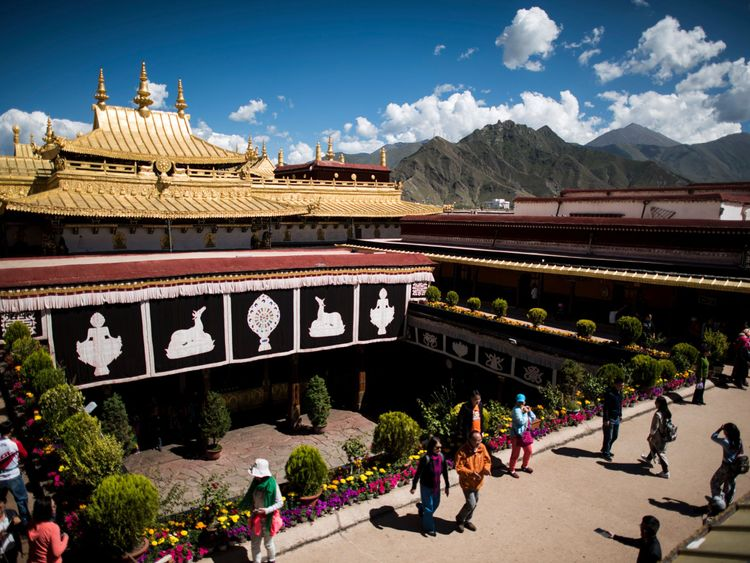 This picture taken on September 10, 2016 shows Chinese tourists on the roof of the Jokhang Temple in the regional capital Lhasa, in China's Tibet Autonomous Region