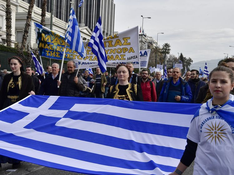 A girl (R) wears a tee-shirt bearing the Vergina Sun, adopted by Greek Macedonians as a symbol of Greek Macedonia, as she holds a flag of Greece during a demonstration to urge the government not to compromise in the festering name row with neighbouring Macedonia, in front of the parliament of Greece, located in the Old Royal Palace (background), at the Syntagma Square in Athens, on February 4, 2018