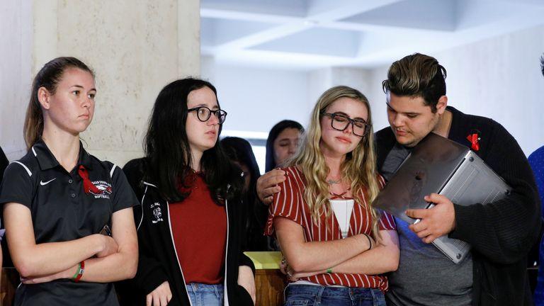 Demitri Hoth (R) consoles fellow Marjory Stoneman Douglas High School student Delaney Tarr
