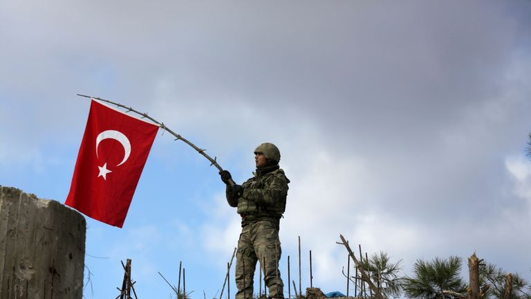 A Turkish soldier waves a flag on Mount Barsaya, northeast of Afrin, Syria January 28, 2018