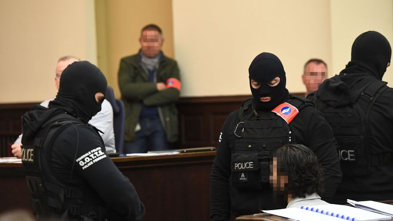 Salah Abdeslam surrounded by special police officers in the Palais de Justice