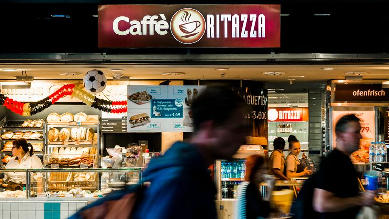 People walk past a Caffe Ritazza outlet at the central train station in Berlin, June 17, 2014.