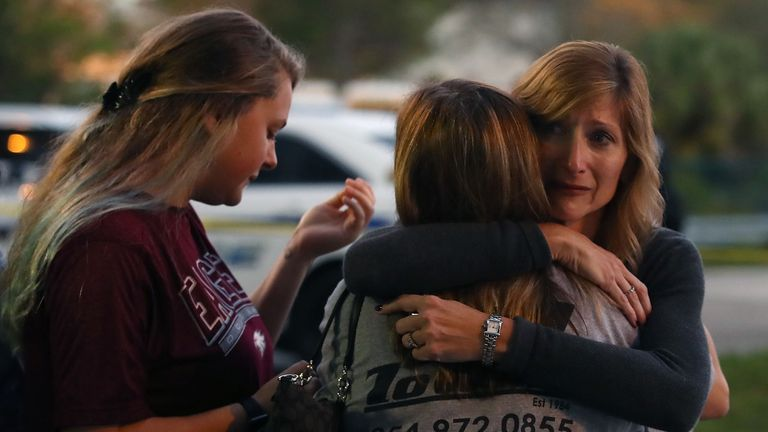 PARKLAND, FL - FEBRUARY 15: Kristi Gilroy (R), hugs a young woman at a police check point near the Marjory Stoneman Douglas High School where 17 people were killed by a gunman yesterday, on February 15, 2018 in Parkland, Florida. Police arrested the suspect after a short manhunt, and have identified him as 19-year-old former student Nikolas Cruz. (Photo by Mark Wilson/Getty Images)