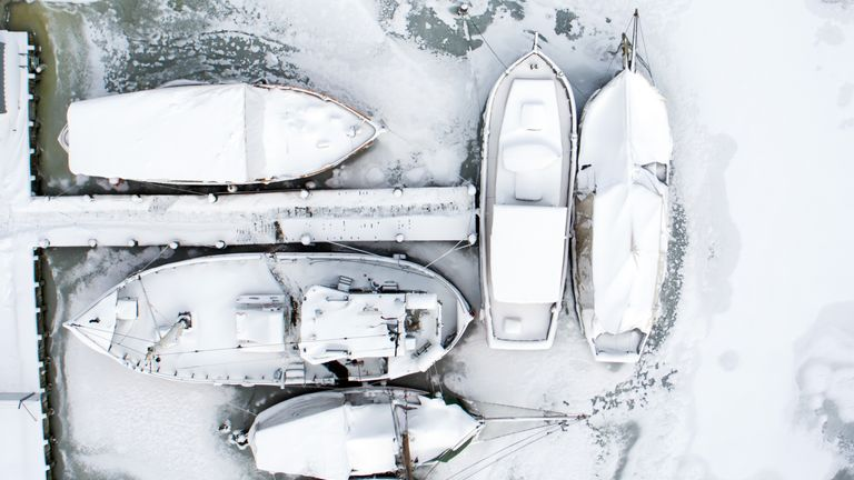 Snow-covered sailing ships moored in Kirchdorf, northeastern Germany