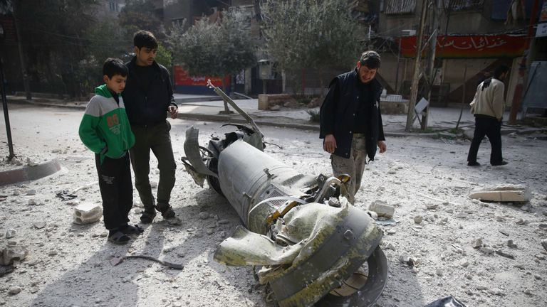 People inspect missile remains in the besieged town of Douma, in eastern Ghouta, in Damascus, Syria