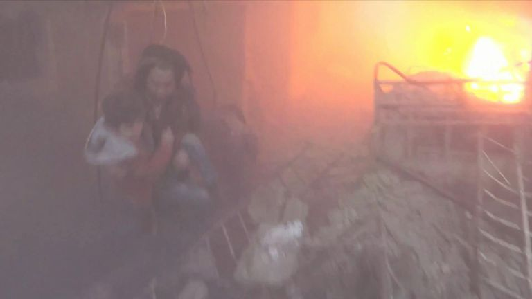A teenager screams for his father in this video and rescuers help people climb out of the rubble of a building, where a fire is actively burning. The Syrian Civil Defense said this video was filmed in Saqba.