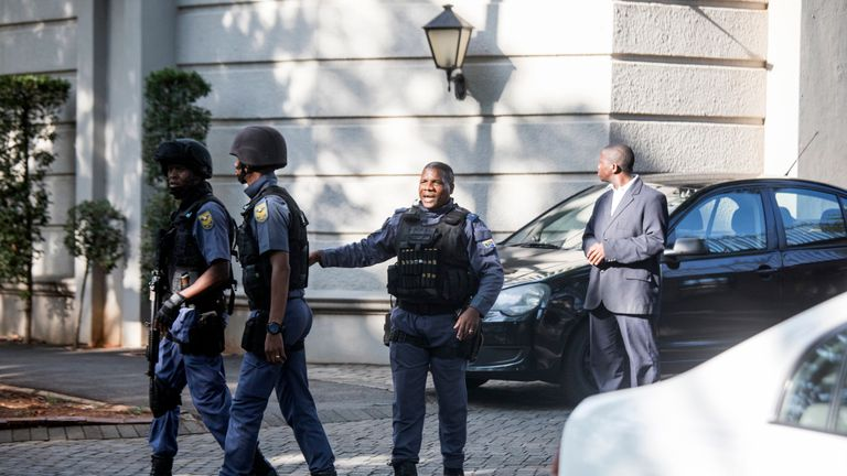 An armed South African Police member outside the Gupta residence