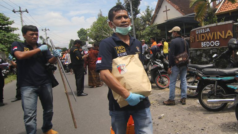Indonesian police carry evidence from the church
