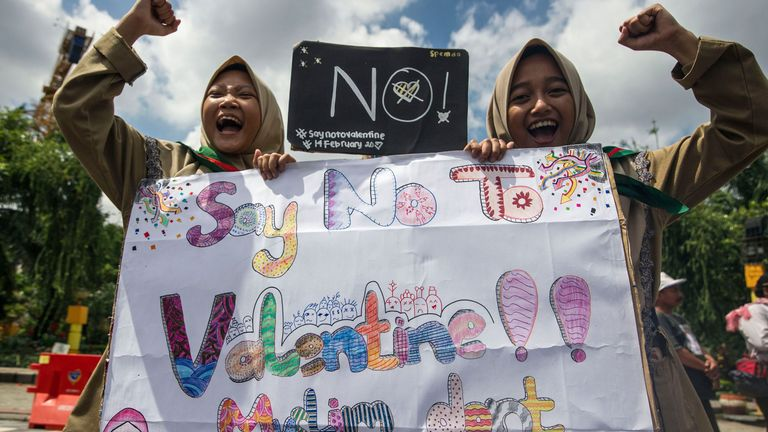 TOPSHOT - Girls from a local boarding school shout during an anti-Valentine's Day rally in Surabaya, East Java province on February 13, 2017. Conservative Indonesian Islamic groups have denounced Valentine's Day, saying it is un-Islamic, promoting promiscuity, casual sex and consumption of alcohol while other groups described the day as foreign cultural influence. About 90 percent of Indonesia's 255 million inhabitants are Muslim but most practise a moderate form of Islam and have lived largely