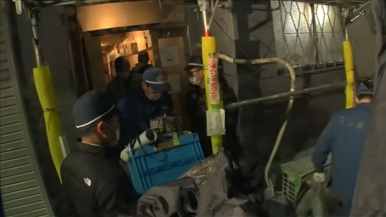 Police leaving the building carrying items from the apartment