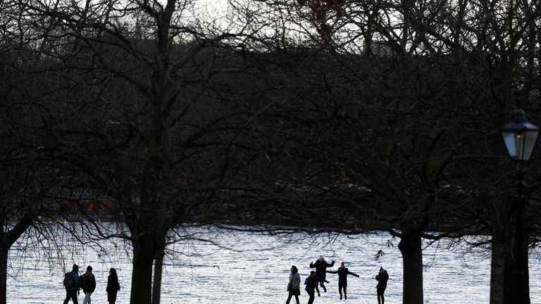 People play in Hyde Park, London, on a snowy Sunday 11 February