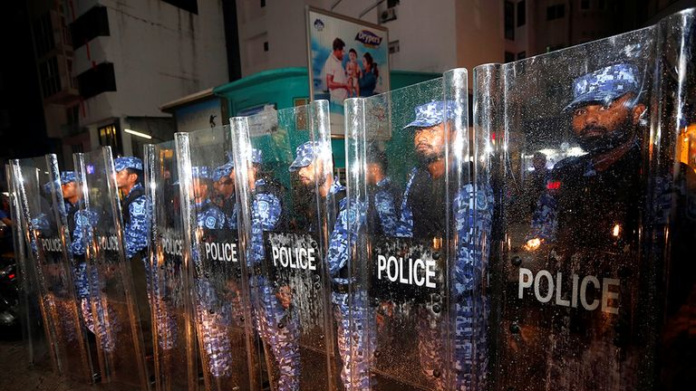 Maldivian police stand guard on a main street during a protest by opposition supporters