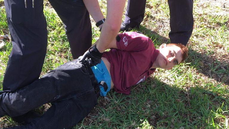 Police detain Nikolas Cruz at the scene of the Parkland school shooting