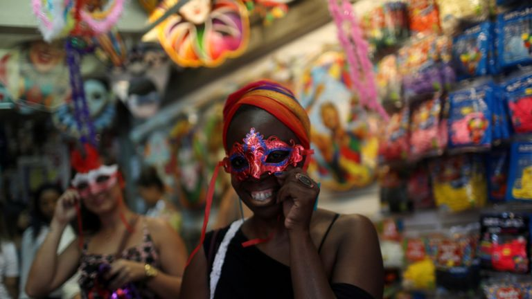 A woman tries on a mask at a street market during carnival festivities in Rio de Janeiro, Brazil February 8, 2018