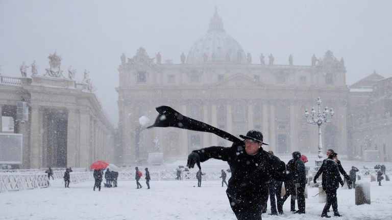 A priest throws a snowball as snow falls in St Peter's Square, Rome