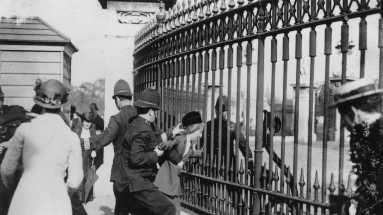 Police trying to remove a Suffragette who chained herself to the railings of Buckingham Palace
