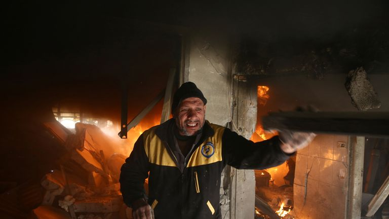 A man makes his way through the rubble after the Syrian government's latest round of airstrikes