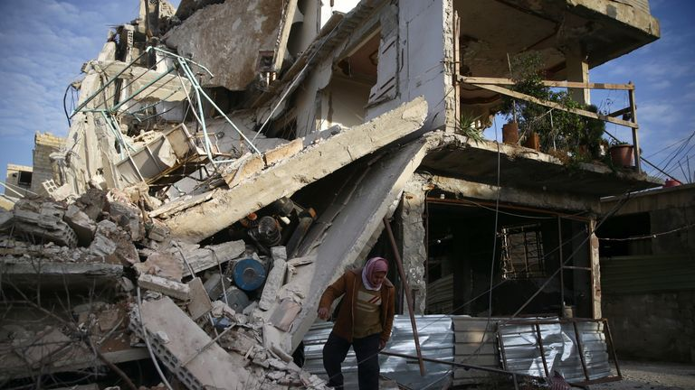 A person inspects damaged building in the besieged town of Douma