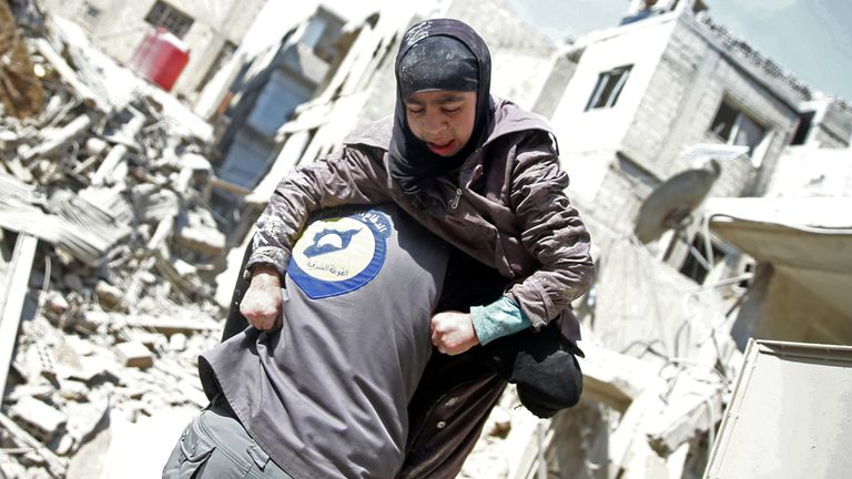 A rescue worker holds an injured girl in the rebel held besieged town of Hamouriyeh, eastern Ghouta, near Damascus, Syria