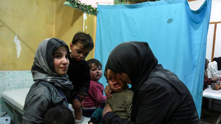 A Syrian woman hugs a crying boy in a make-shift clinic