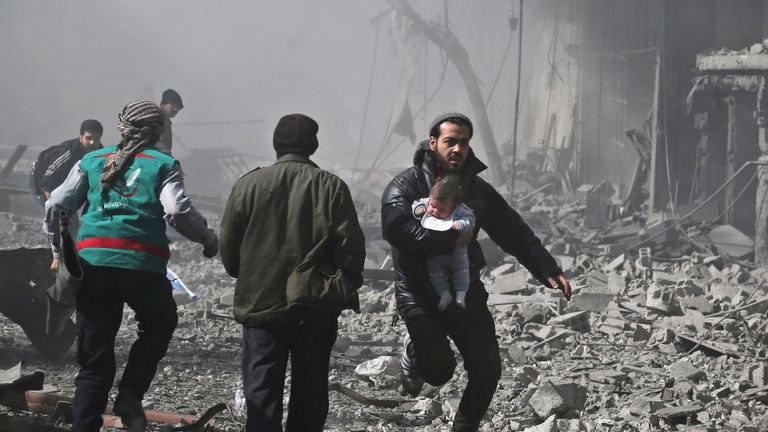 A Syrian man carries an infant rescued from the rubble of buildings following the air strikes