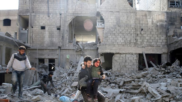 A man carries an injured boy out of a bombed building in Ghouta