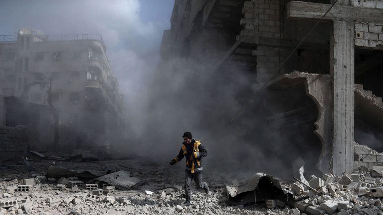 A White Helmets volunteer in the aftermath of an air raid in Saqba, eastern Ghouta