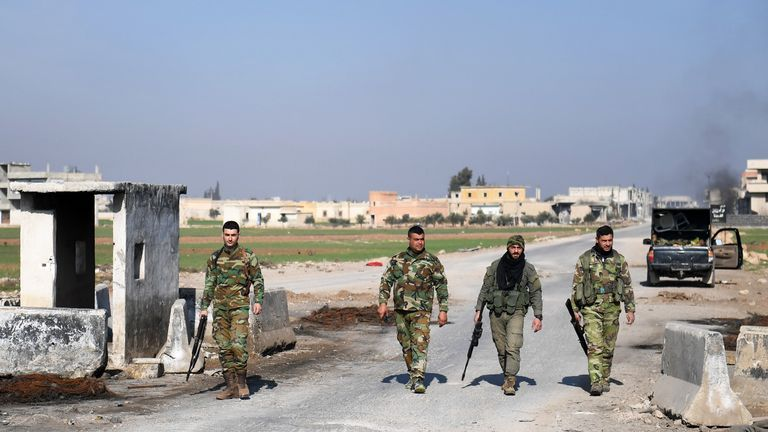 Syrian government forces walk past an abandoned checkpoint in Abu al-Duhur