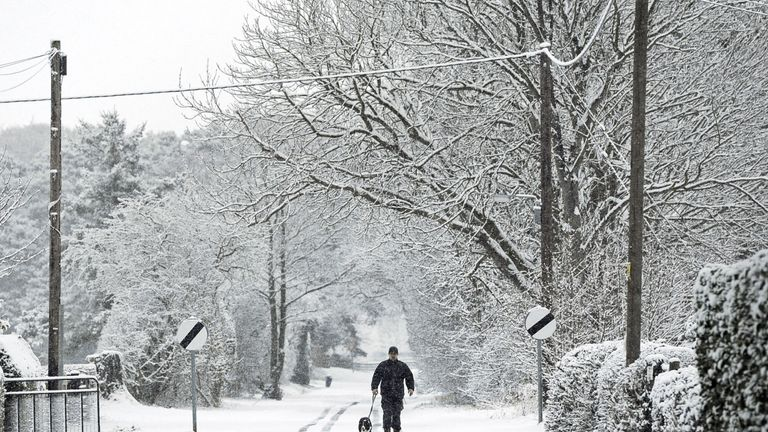 A man walks his dog down a snow covered lane near Malton in North Yorkshire