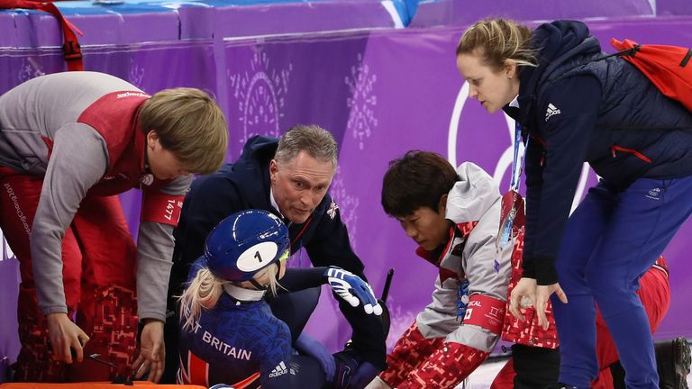 Elise Christie is treated by medics before being stretchered off the ice